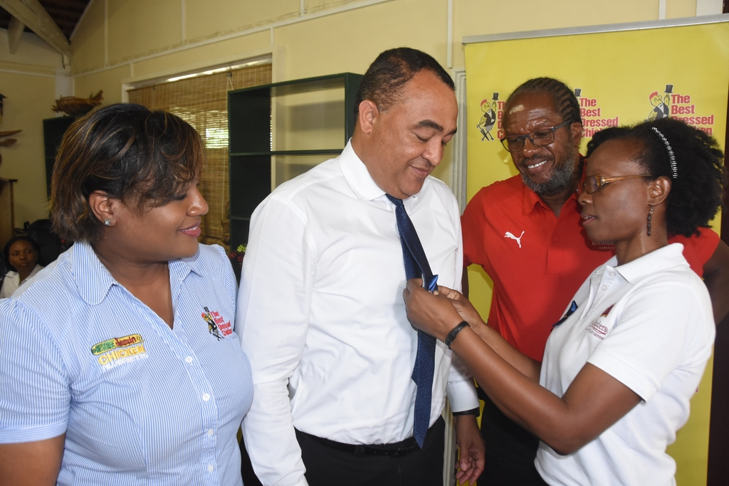 Deniese Badroe (right), Director, Business Development Division, Jamaica Association for the Deaf pins on a blue ribbon on Dr. Christopher Tufton (second left), Minister of Health and Wellness, while Lorraine Kemble (left), Brand Manager, The Best Dressed Chicken and Alfred 'Frano' Francis (second right), Race Director, Running Events Jamaica look on.