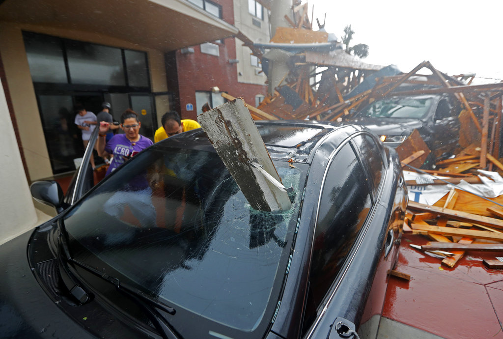 A woman checks on her vehicle as Hurricane Michael passes through, after the hotel canopy had just collapsed, in Panama City Beach, Florida. (AP Photo/Gerald Herbert)