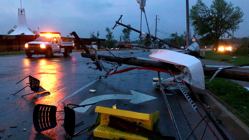 Plastic chairs lie in the road and metal from a damaged gas station roof is twisted around a downed power line in Jefferson City Missouri Thursday, May 23, 2019. The National Weather Service has confirmed a large and destructive tornado has touched down in Missouri's state capital, causing heavy damage and trapping multiple people in the wreckage of their homes. (AP Photo/David A. Lieb)