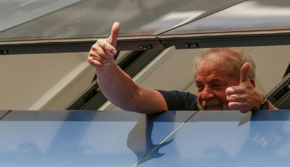"""L'ex-président brésilien Lula saluant ses partisans depuis une fenêtre peu avant son incarcération pour corruption, en avril 2018. Veuf depuis deux ans, Lula, 73 ans, est """"amoureux"""" et a prévu de se remarier s'il sort de prison, a annoncé un ancien ministre. Photo Miguel SCHINCARIOL. AFP"""