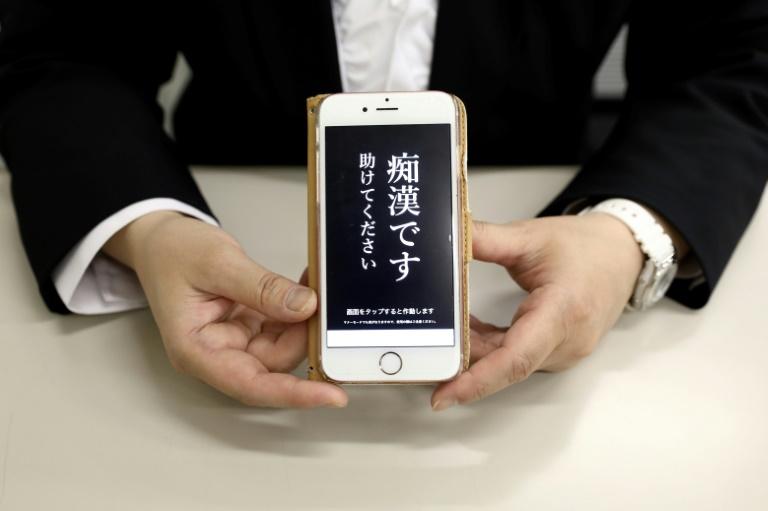 """Un responsable de la police tient un téléphone contenant l'application """"Digi police"""", à Tokyo, le 13 mai 2019"""
