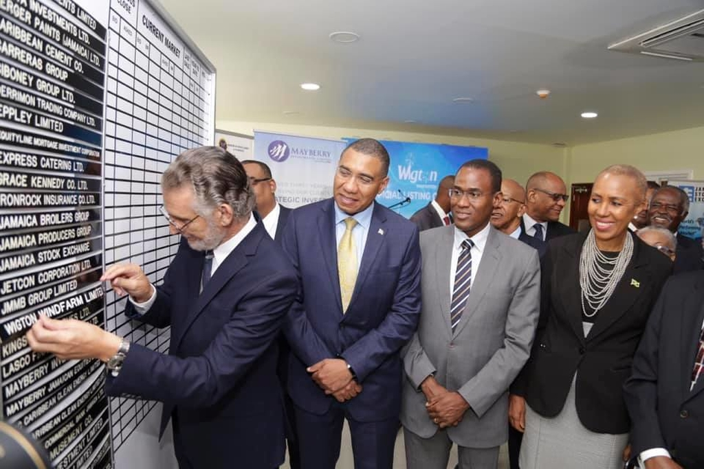 Prime Minister, Andrew Holness (second left), observes as Chairman, Petroleum Corporation of Jamaica, Russell Hadeed (left), inserts the strip signifying Wigton Windfarm's official listing on the JSE. Also sharing moment are (from third left) Minister of Finance, Dr. the Hon. Nigel Clarke; Minister of Science, Energy and Technology, Fayval Williams; and General Manager, Wigton Windfarm, Earl Bennett.(Photo credit, Andrew Holness, Facebook)