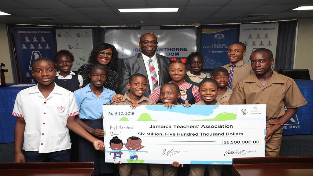 Head of Group Marketing, Sagicor Group Jamaica, Alysia White (2nd left), and President of the Jamaica Teachers' Association (JTA), Dr. Garth Anderson (centre, back row), share a moment with student athletes, posing with a symbolic cheque from the Sagicor Foundation, at the press launch of the 36th JTA/Sagicor National Athletic Championships. The launch was held on Tuesday, April 30, at the JTA's head office in Kingston.
