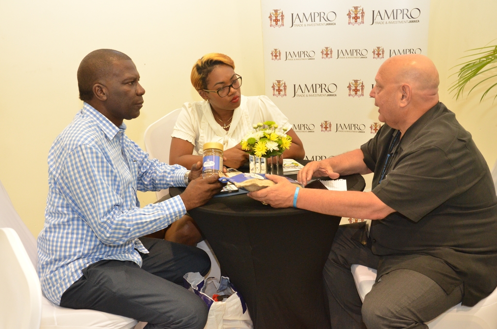 Norman Grant, CEO, Mavis Bank Coffee Factory (left) and Janice Hall, Former Trade Marketing Manager at Mavis Bank Coffee Factory (centre) speak to a  buyer at the 2017 staging of the Jamaica International Exhibition (JIE).