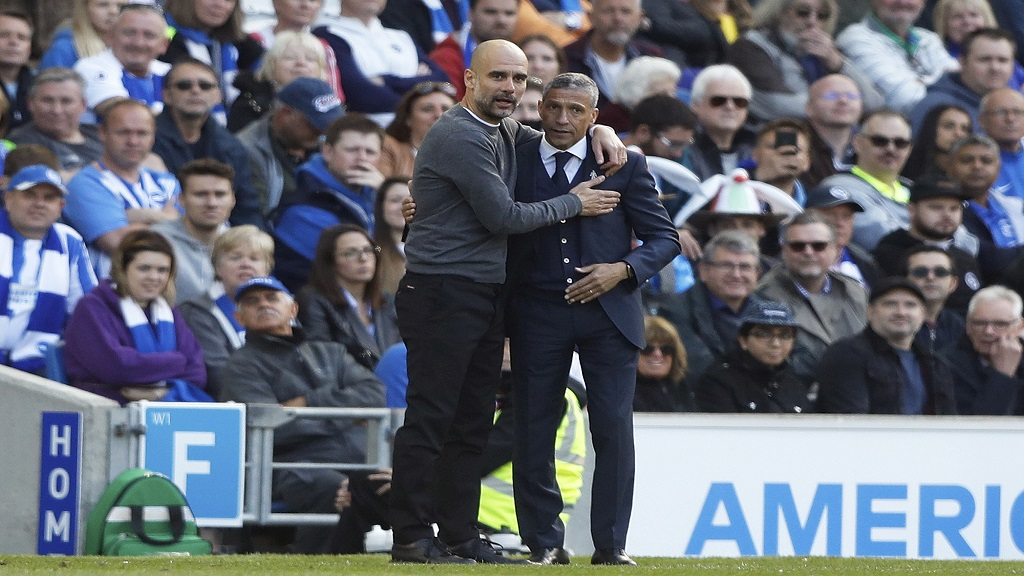 Manchester City coach Pep Guardiola and Brighton manager Chris Hughton, right, embrace each other during the English Premier League match between Brighton and Manchester City at the AMEX Stadium in Brighton, England, Sunday, May 12, 2019. (AP Photo/Frank Augstein)