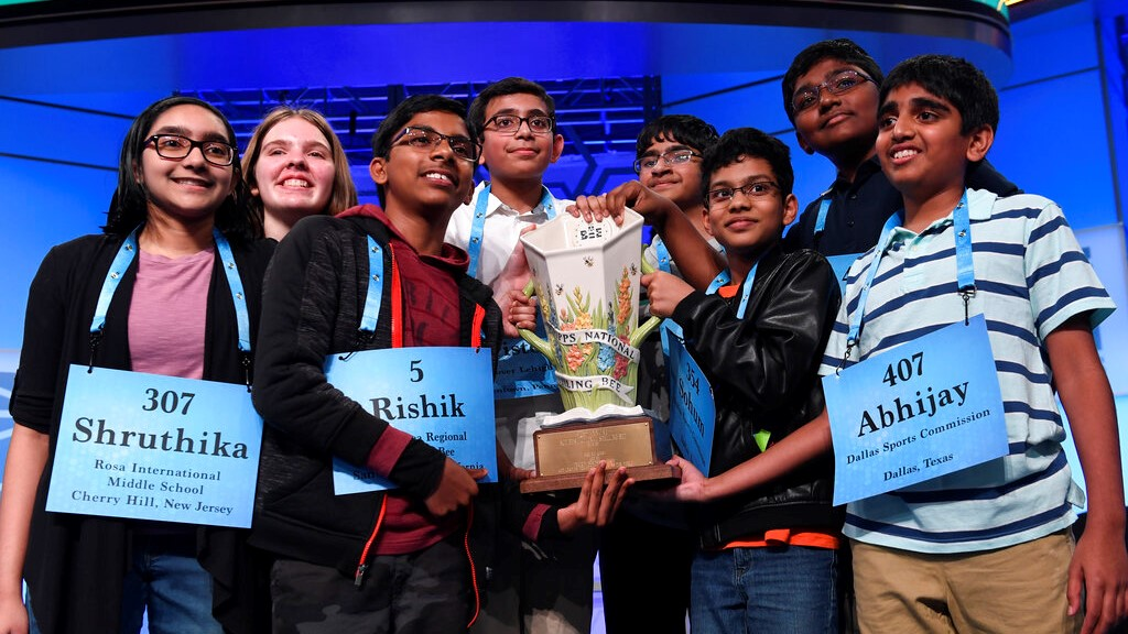 The eight co-champions of the 2019 Scripps National Spelling Bee, (l-r) Shruthika Padhy, 13, Erin Howard, 14, Rishik Gandhasri, 13, Christopher Serrao, 13, Saketh Sundar, 13, Sohum Sukhatankar, 13, Rohan Raja, 13, and Abhijay Kodali, 12, hold the trophy at the end of the competition in Oxon Hill, Md., Friday, May 31, 2019. (AP Photo/Susan Walsh)