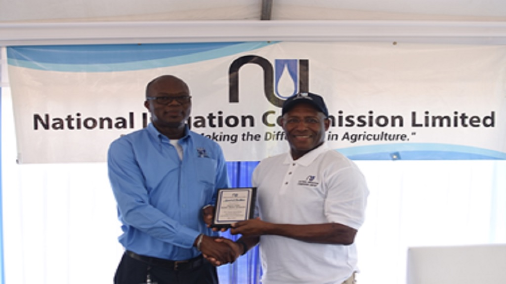 Chairman of the National Irrigation Commission, Senator Aubyn Hill (right) presents Principal of the Ebony Park HEART Trust Academy, Collie Clarke (left) with an award of excellence during the tour of the farm.