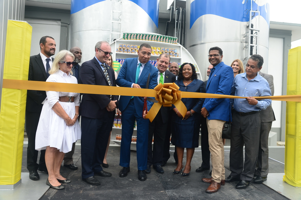 Prime Minister Andrew Holness cuts the ribbon signifying the official launch of the consolidated Serge Island Dairies plant at Bogwalk, St Catherine on Tuesday. (Photo contributed).