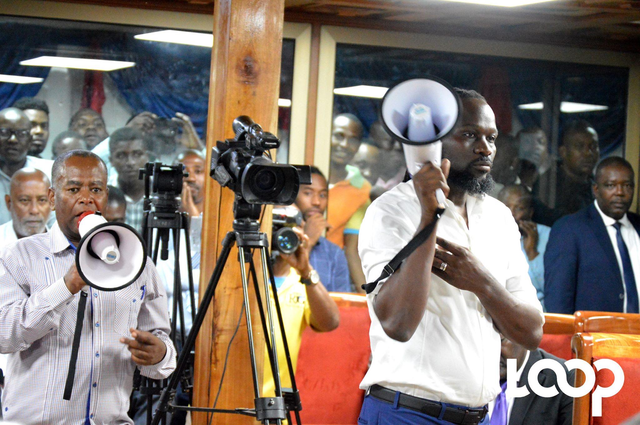 Les sénateurs de l'opposition, mégaphone en main, perturbant la séance de ratification de la politique générale de Jean MIchel Lapin