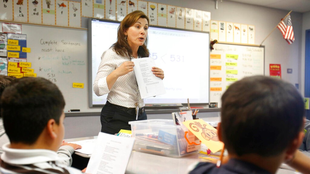 In this June 12, 2013 file photo second-grade teacher Vickie Boudouris goes over a an English work sheet with her students at the Cordova Villa Elementary School, in Rancho Cordova, Calif. (AP Photo/Rich Pedroncelli, File)