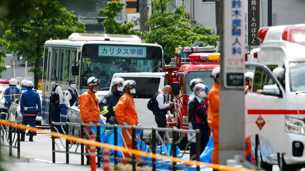 A school bus, centre, is parked at the scene of an attack in Kawasaki, near Tokyo Tuesday, May 28, 2019. A man wielding a knife attacked commuters waiting at a bus stop just outside Tokyo during Tuesday morning's rush hour, Japanese authorities and media said. (Kyodo News via AP)