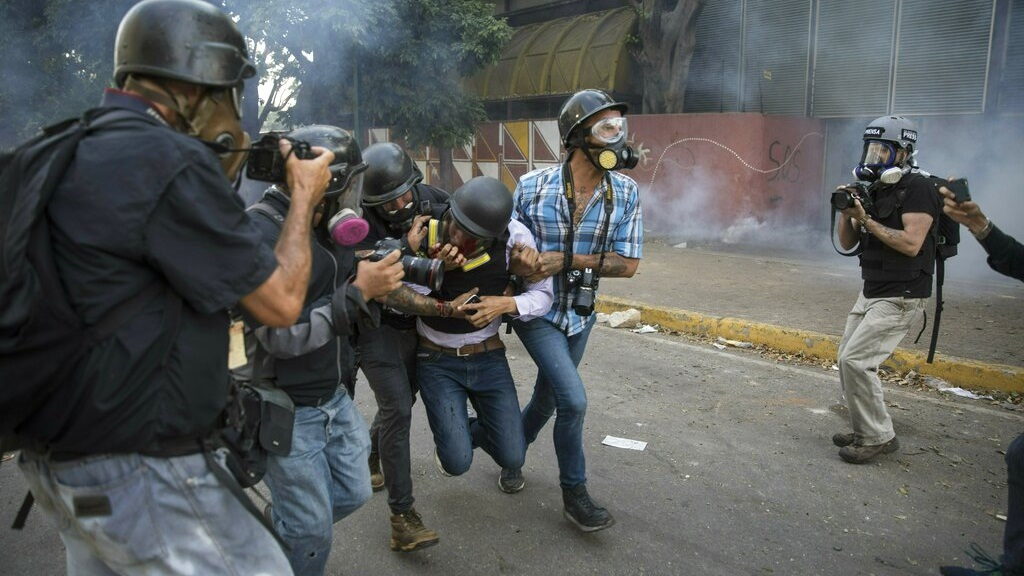 Journalists help reporter Gregory Jaimes, holding a VPITV microphone, who was injured while covering clashes between security forces and anti-government protesters in the Altamira neighborhood of Caracas, Venezuela, Wednesday, May 1, 2019. (AP Photo/Ariana Cubillos)