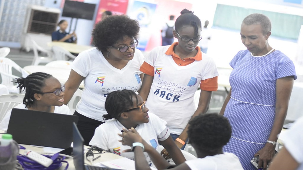 Technology Minister Fayval Williams engages Caribbean Hackathon participants at the Chinese Benevolent Association on Tuesday, while Bridget Lewis, co-founder of event organiser SheLeadsIT, looks on. (PHOTOS: Marlon Reid)