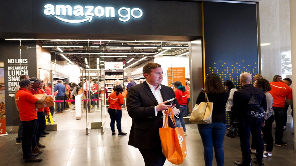 A customer carries his shopping bag as she walks out of a newly-opened Amazon Go store, Tuesday, May 7, 2019 in New York. (AP Photo)