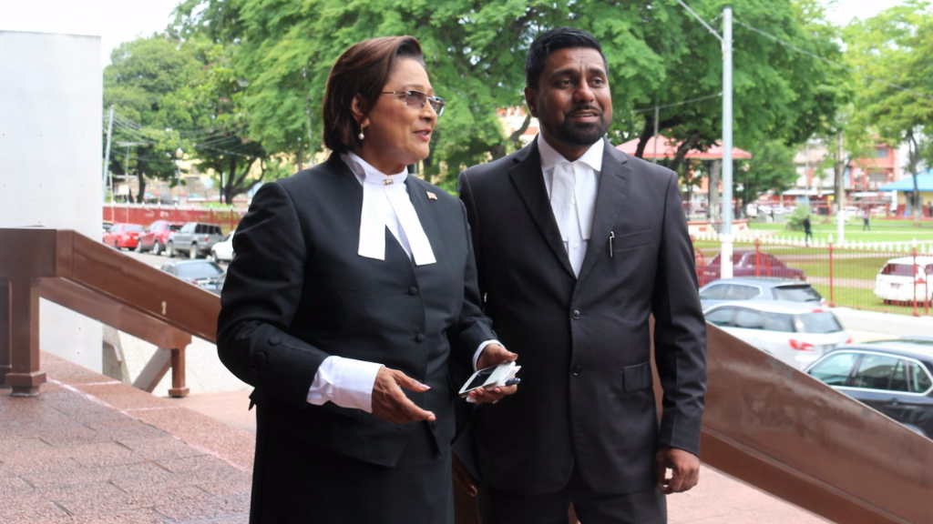 Opposition Leader Kamla Persad-Bissesar (left), Opposition Senator Gerald Ramdeen (right) stand outside the POS High Court on July 13.