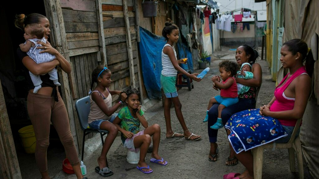 "Families gather outside their home in the ""Aguerridos Liberator"" shanty town in Caracas, Venezuela, Thursday, May 9, 2019. (AP Photo/Rodrigo Abd)"