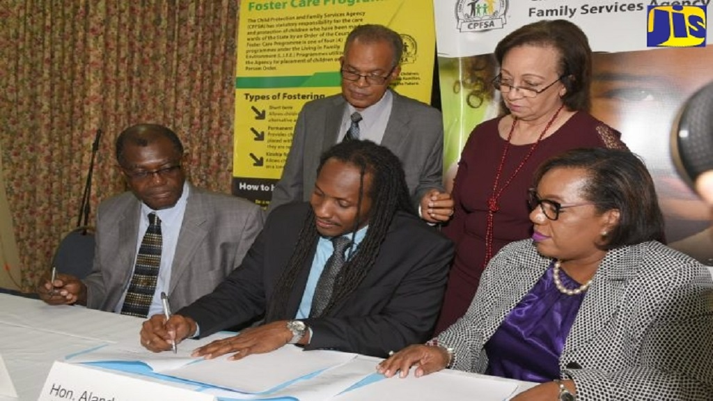 State Minister for Education, Youth and Information, Alando Terrelonge, signs a service agreement in Kingston recently between the Child Protection and Family Services Agency and Family Life Ministries for a pilot foster care project. Waiting to sign are Chief Executive Officer of FLM, Dr Barry Davidson (seated left); and CEO of CPFSA, Rosalee Gage-Grey (seated right). Looking on are FLM board members, Arnold Aiken and Professor Maureen Samms-Vaughan.