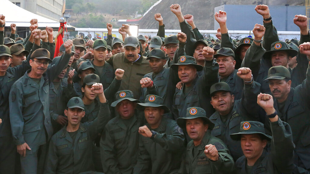 "In this photo released by Miraflores Press Office, Venezuela's President Nicolas Maduro, center left, poses for a photo with troops at Fort Tiuna, in Caracas, Venezuela, Thursday, May 2, 2019. Flanked by commanders, Maduro said Thursday that the military must be prepared to combat ""traitors"", two days after opposition leader Juan Guaidó called for the military to turn against Maduro. (Jhonn Zerpa/Miraflores Press Office via AP)"