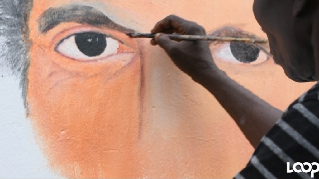 An artist putting the finishing touches on a mural of late Prime Minister Edward Seaga in Tivoli Gardens on Tuesday.