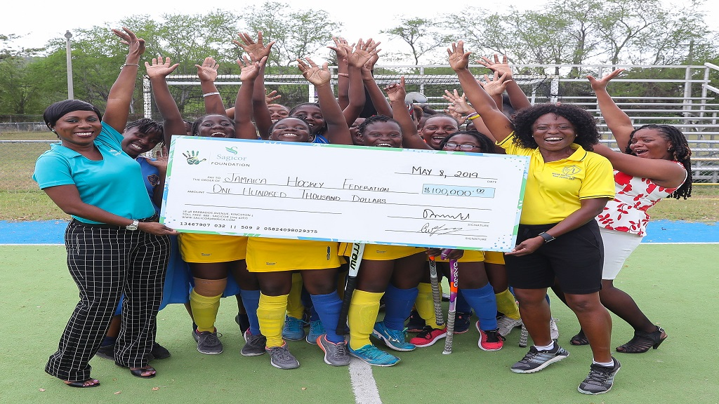Shelly-Ann Morgan (left), Manager, Investment Client Services, Sagicor Investments and Sagicor Foundation volunteer made the presentation to AnnMarie Smith, MGHS hockey team coach, at the Mona Hockey Field on Wednesday.