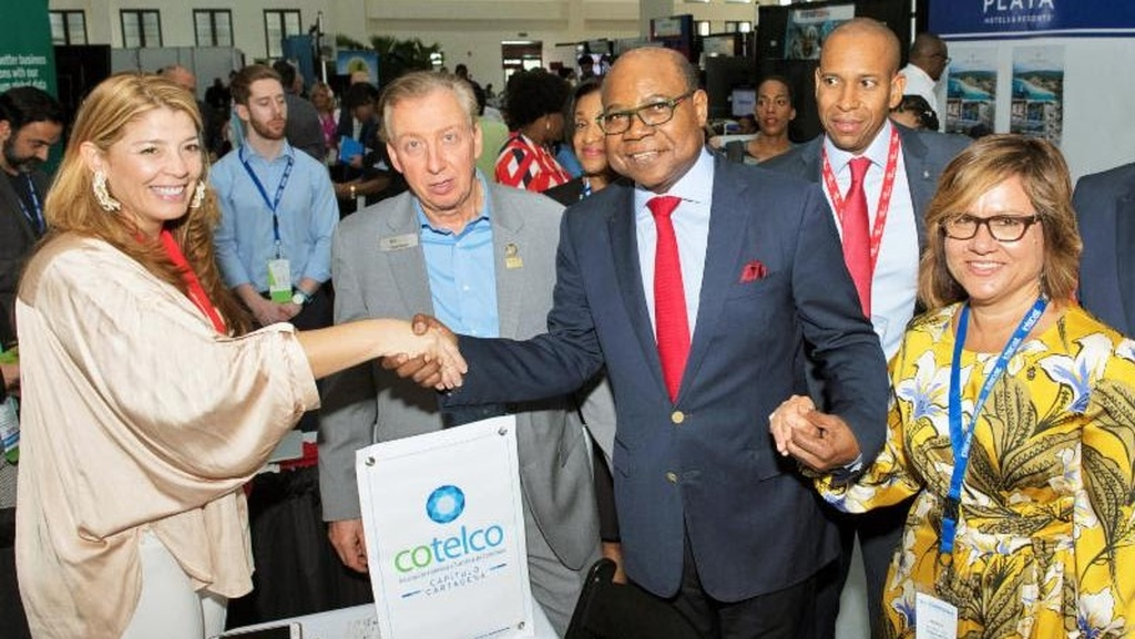 Monica Mass Tinoco, Executive Director of COTELCO Cartagena (left), greets Jamaica's Minister of Tourism Edmund Bartlett during Caribbean Travel Marketplace in Montego Bay. From left are Frank Comito, CEO of the Caribbean Hotel and Tourism Association (CHTA); David Noel, President and CEO of Scotiabank Group Jamaica; and CHTA President Patricia Affonso-Dass.