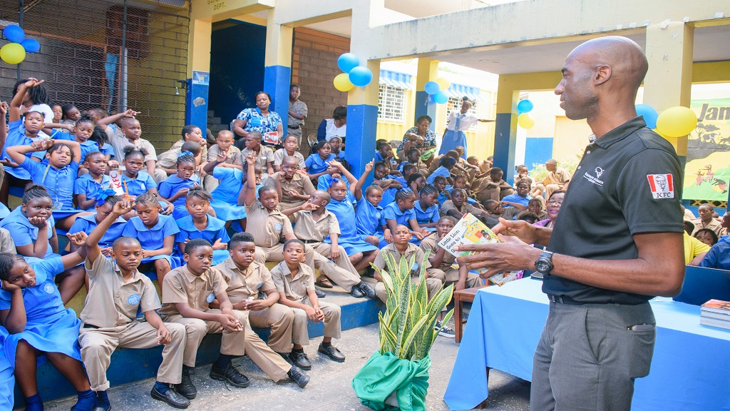 Andrei Roper, brand manager for Restaurants of Jamaica conducts a reading exercise at the Harbour View Primary during Read Across Jamaica Day.