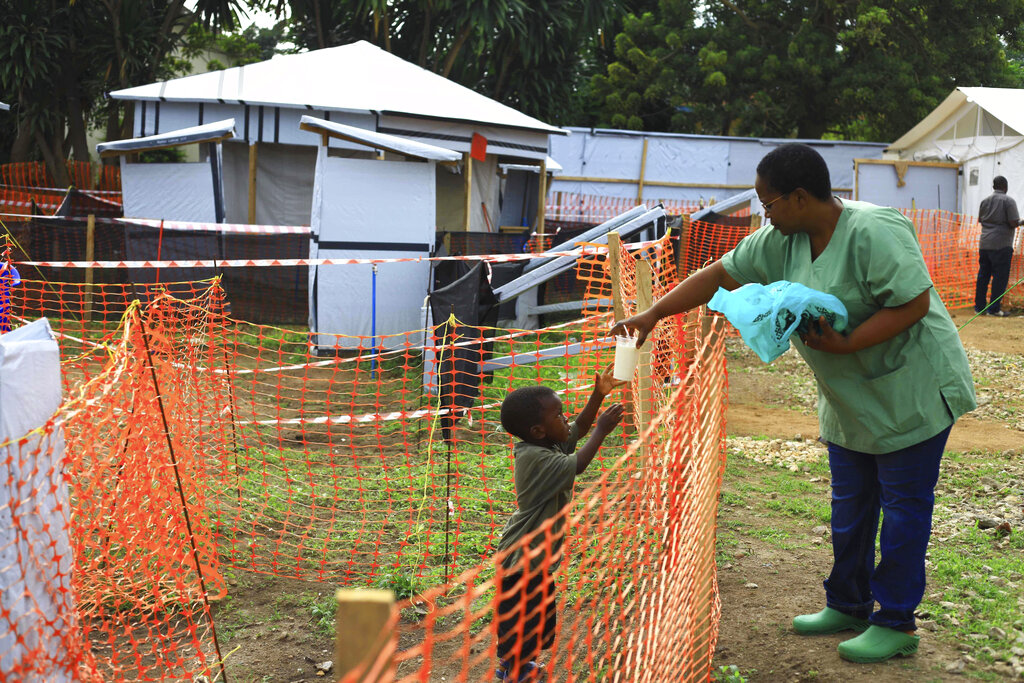 In this Sunday, Sept. 9, 2018 file photo, a health worker feeds a boy suspected of having the Ebola virus at an Ebola treatment centre in Beni, Eastern Congo. (AP Photo/Al-hadji Kudra Maliro, File)
