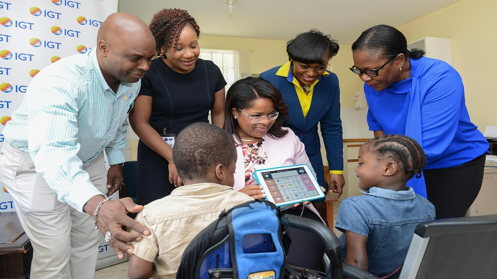 Children of the Gift of Hope Home in Manchester take a moment to observe the features on new iPad equipped with an assistive learning programme donated by IGT.