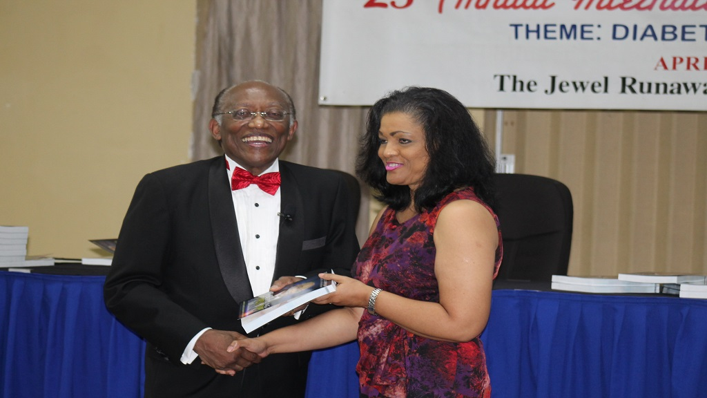 A beaming Professor Morrison presents a copy of his autobiography to  Lurline Less, Chairperson of the Diabetes Association of Jamaica.