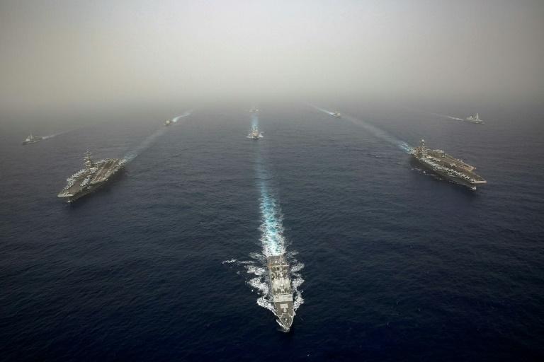 Navy Office of Information/AFP / Jeremiah BarteltPhoto fournie par l'US Navy le 24 avril 2019 montrant le porte-avions USS Abraham Lincoln et son escorte. Le navire croise actuellement dans le Golfe