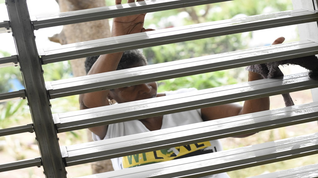 A woman cleans a window during the Labour Day project on Thursday at the Open Arms Drop-In Centre along Windward Road in Kingston. (PHOTOS: Marlon Reid)