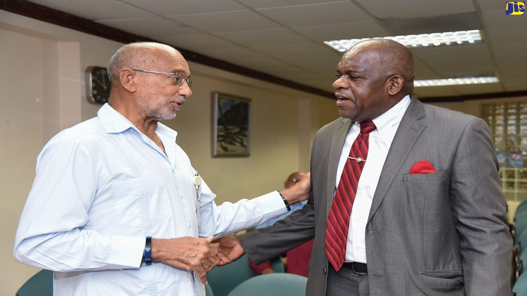 Director of the Centre for Disability Studies at the University of the West Indies (UWI), Mona Campus, Senator Floyd Morris (right), greets patron of the National Child Month Committee (NCMC), Douglas Orane, at the launch of Child Month 2019, which was held recently at GraceKennedy's office in downtown Kingston.
