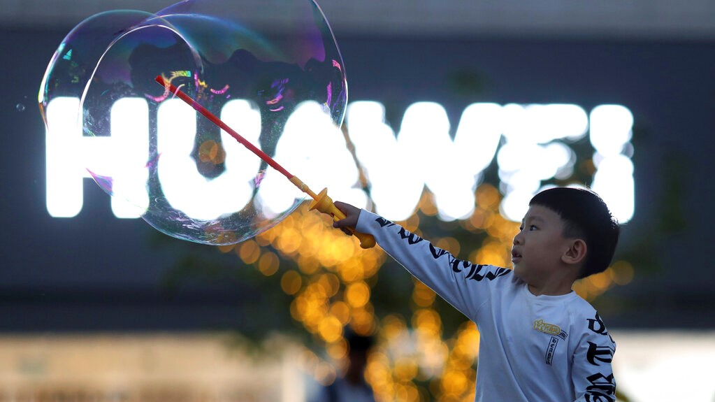 In this photo taken Monday, May 20, 2019, a child plays with bubbles near the logo for tech giant Huawei in Beijing. (AP Photo/Ng Han Guan)