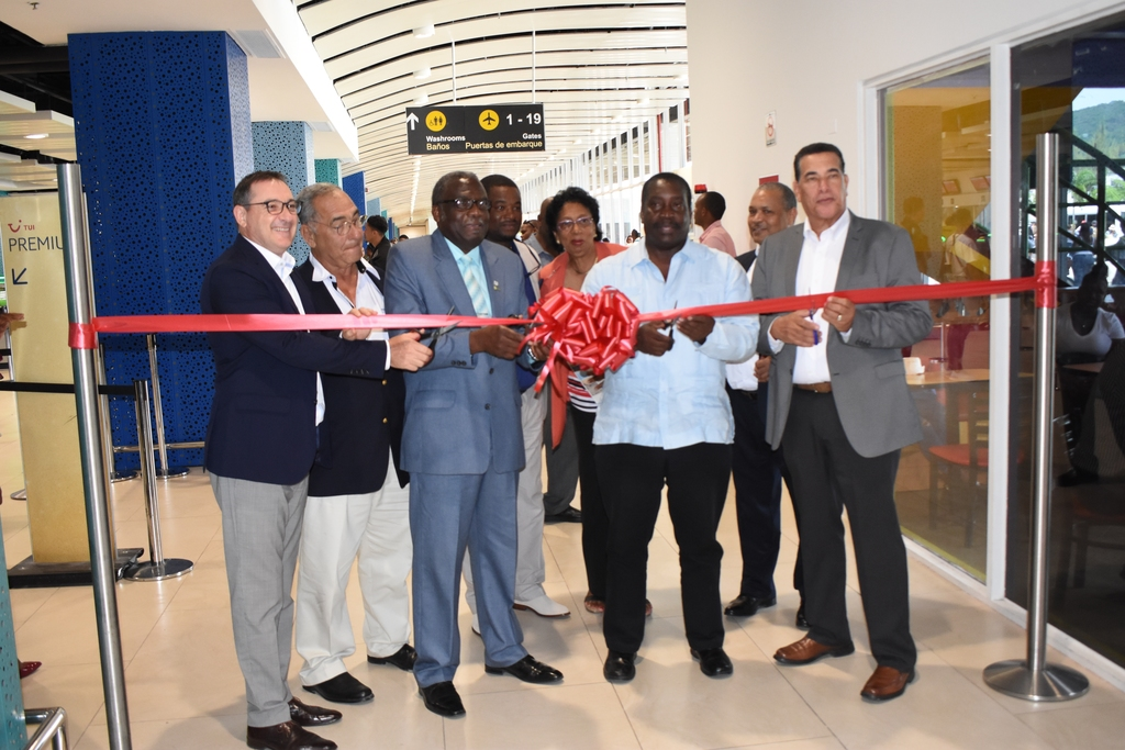 Transport and Mining Minister, Robert Montague (2nd right) cutting ribbon to symbolically open the newly renovated ticketing hall at the Sangster International Airport in Montego Bay last Friday.