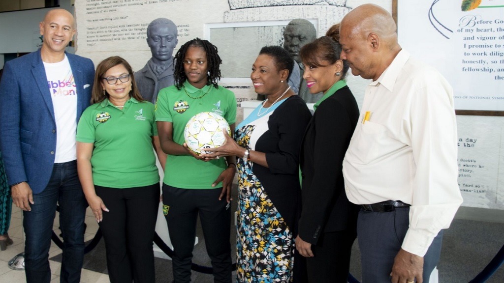 Sport Minister Olivia Grange (3rd right), receives from Reggae Girlz captain Konya Plummer a football signed by members of the team. The Reggae Girlz departed Jamaica on Monday, May 20, 2019 to begin final preparation for the FIFA Women's World Cup in France. Sharing the moment are JFF President, Michael Ricketts (right) and from Caribbean Airlines: Zachary Harding, Director; Alicia Cabrera, Senior Marketing Manager; and Trudy Chin, General Manager.