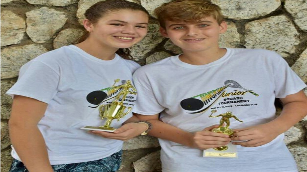 All Jamaica Under 15-17 girls' champion, Savannah Thomson (left) and All Jamaica Under 15 boys' champion, Tobias Levy pose with their trophies after winning their respective age groups at the Tingrinners Age Group Squash Tournament held recently at the Liguanea Club in Kingston.
