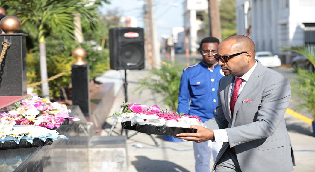Town Clerk Robert Hill lays a wreath at the Secret Gardens in downtown, Kingston on Sunday.