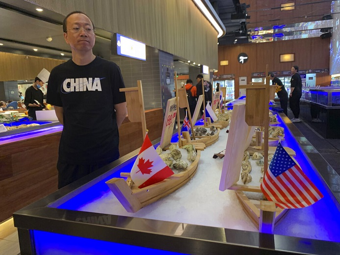 A shopper eyes display of seafood including oysters from the U.S. at a supermarket in Beijing on Tuesday, May 14, 2019. China announced higher tariffs Monday on $60 billion worth of American goods in retaliation for President Donald Trump's latest penalties on Chinese products. (AP Photo/Ng Han Guan)