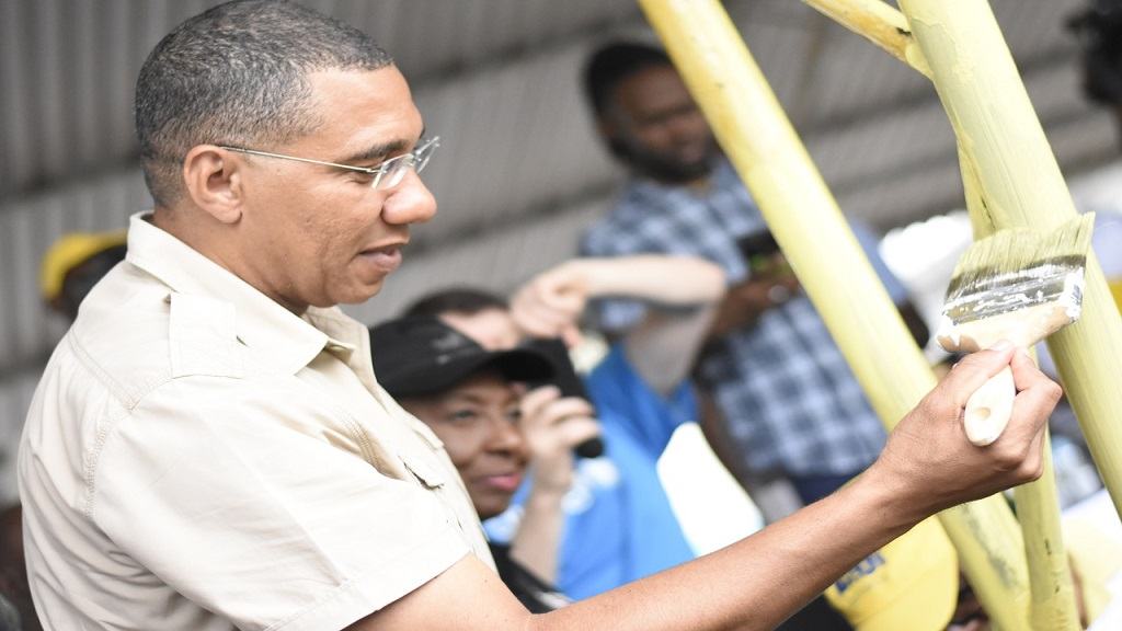 Prime Minister Andrew Holness painting a rail at Papine High School on Thursday. (PHOTOS: Marlon Reid)