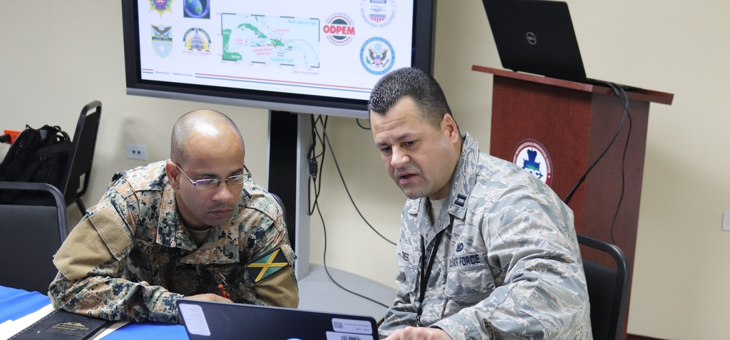 Member of the DC National Guard examines Jamaica's National Disaster Action Plan with a member of the Jamaica Defense Force, as part of a military-to-military planning exercise.