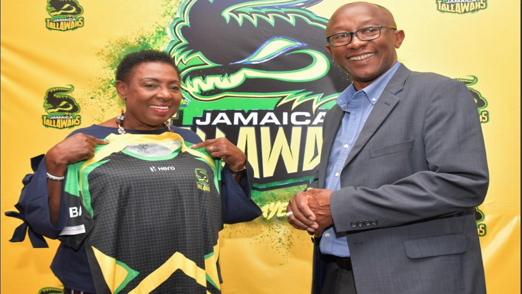 Sports Minister Olivia Grange (left) receives a Jamaica Tallawahs shirt from Jefferson Miller, Chief Executive Officer of the franchise on Saturday at the Jamaica Pegasus Hotel.