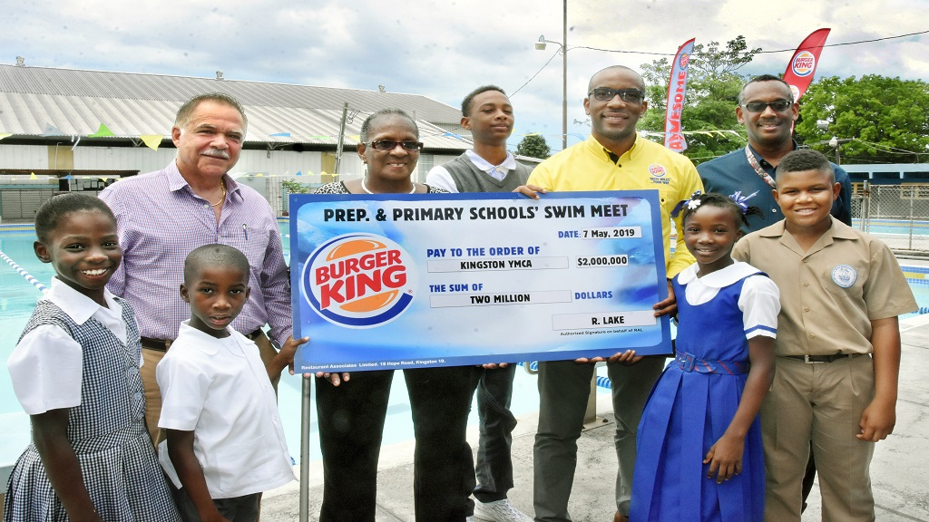Young student swimmers participate in the presentation of the Burger King cheque of $2m by Nicholas Mundell (2nd right back row), Brand Manger, Burger King at the media launch of the 2019 Burger King/YMCA Preparatory and Primary School Swim Meet at the YMCA Kingston Pool on May 7, 2019.