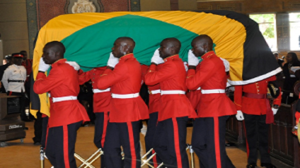 The casket bearing the remains of former Governor General, Sir Howard Cooke, draped in the Jamaican flag, being taken into the Holy Trinity Cathedral by the Jamaica Defence Force (JDF) bearer party in 2014.