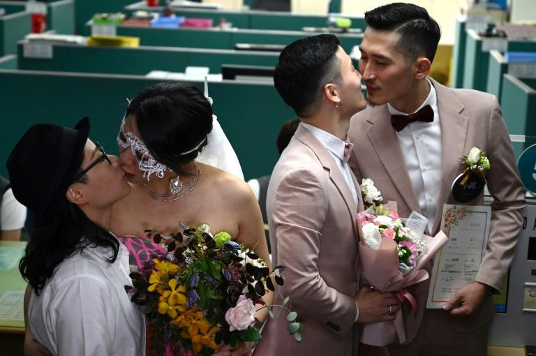 Les premiers couples homosexuels officiellement mariés s'embrassent, à Taipei, le 24 mai 2019