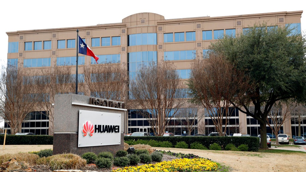 In this Thursday, March 7, 2019 file photo, the Texas state flag files outside the Huawei Technologies Ltd. business location in Plano, Texas. (AP Photo/Tony Gutierrez, File)