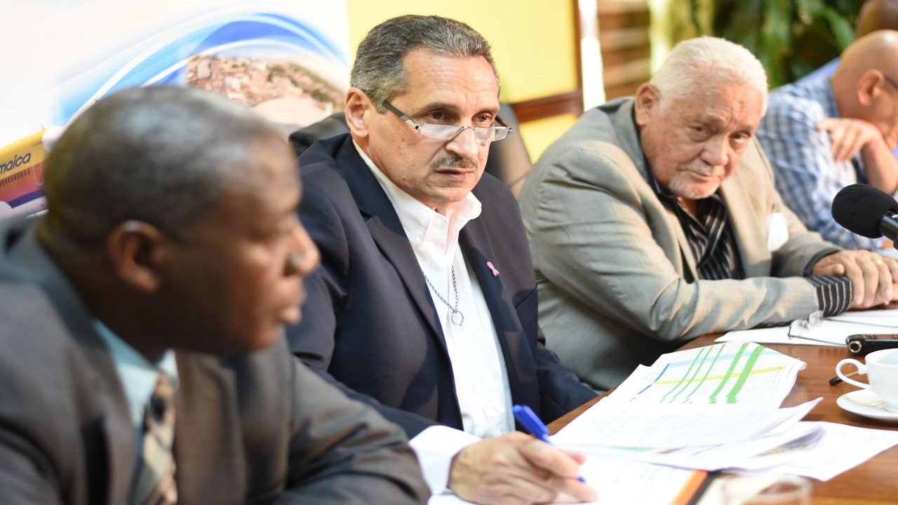 In this December 2017 file photo, JUTC managing director Paul Abrahams (centre) addresses journalists at a press conference. Seated to his left is then Transport Minister Mike Henry.