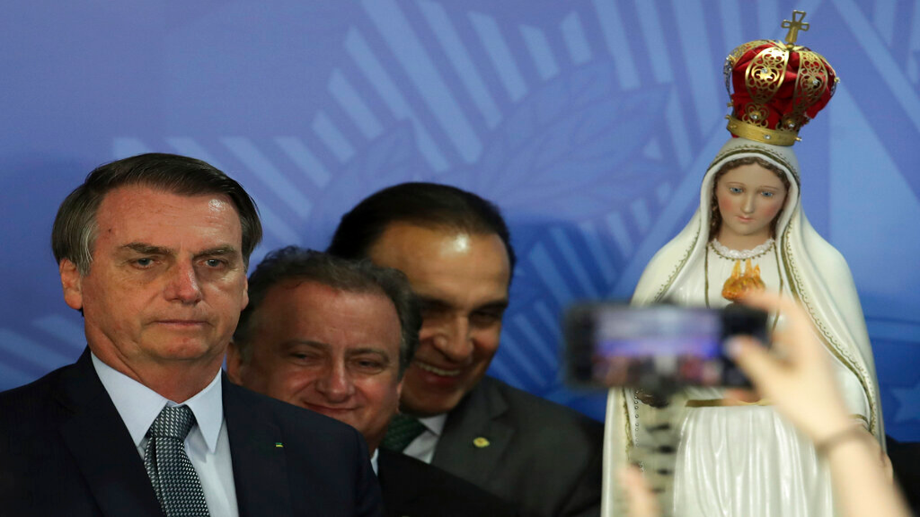 Brazil's President Jair Bolsonaro poses for photos with a statue of Our Lady of Fatima,during a Catholic ceremony at which he dedicated his nation to the Immaculate Heart of Mary at Planalto presidential palace in Brasilia, Brazil, Tuesday, May 21, 2019. (AP Photo/Eraldo Peres)