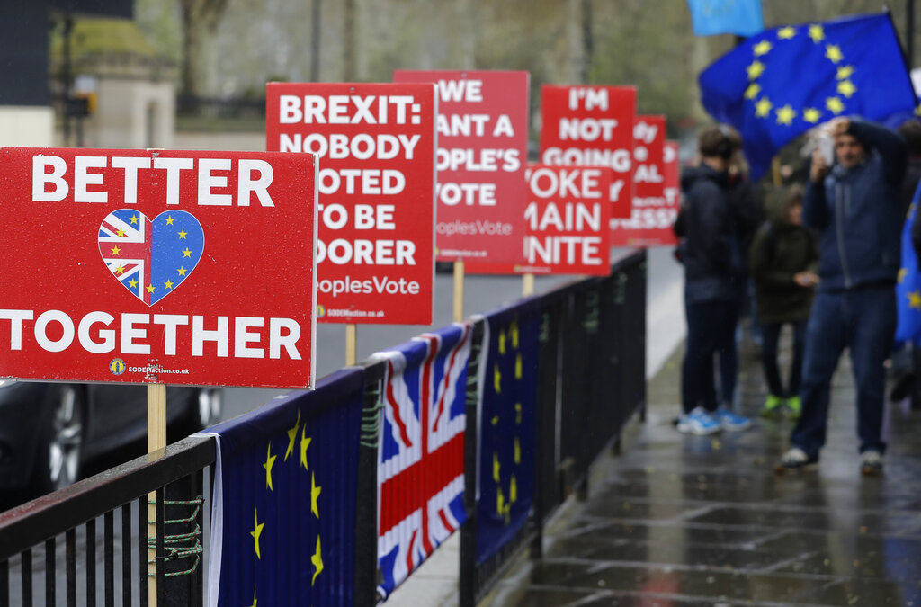 A passerby takes a picture of banners near parliament, in London, Tuesday, April 9, 2019. (AP Photo/Kirsty Wigglesworth)
