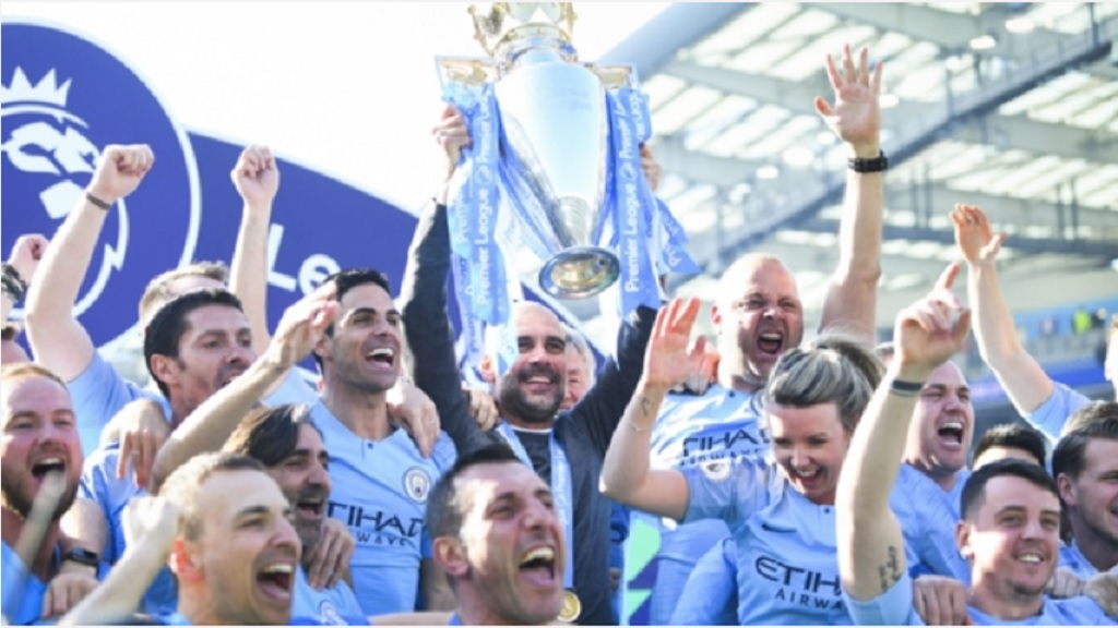 Pep Guardiola celebrates with the Premier League trophy.