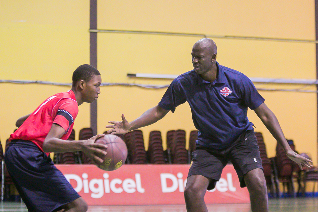 T&T's Malique Lewis tries to dribble past NBA legend & Former NCAA Coach Mamadou N'Diaye at the Digicel Jumpstart Youth Basketball Camp at the Center of Excellence, Macoya. Mamadou who is 7 ft tall, was in T&T as an NBA International Coach participating in the Digicel training programme.